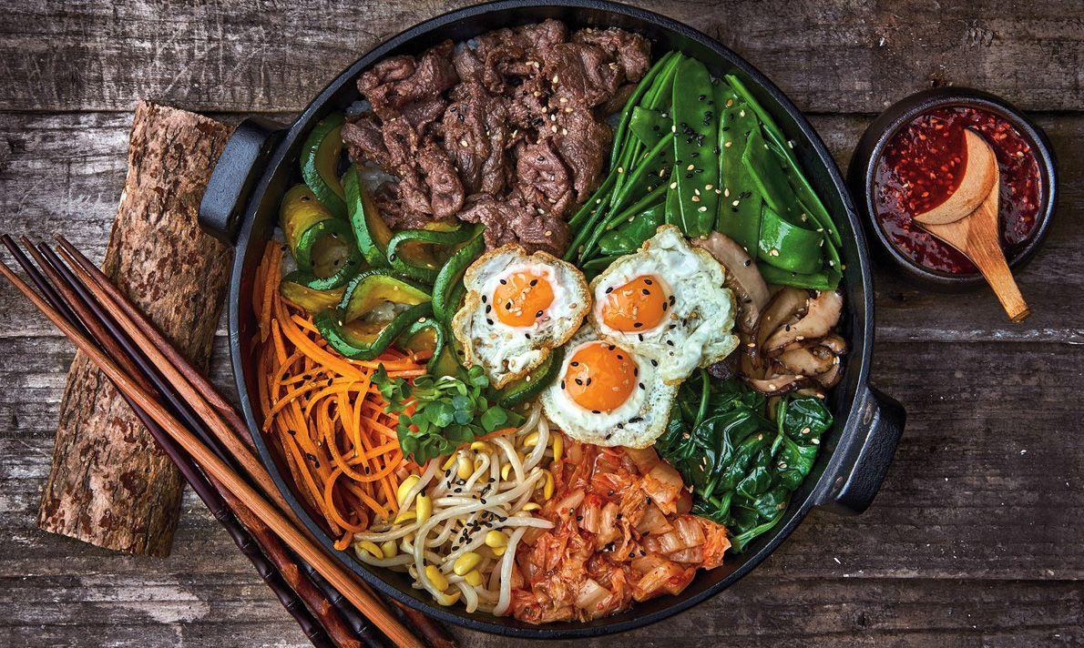 Bibimbap Hàn Quốc làm món ăn có cả hương vị lẫn hình thức. Món ăn bao gồm các nguyên liệu rau củ quả tươi, nấm, thịt bò hoặc thịt heo ( nếu bạn không ăn được thịt bò),.... Điểm nhấn của món ăn chính là sự kết hợp hài giữa các nguyên liệu với nhau tạo nên cái cảm giác khó quên khi ta lần đầu nếm thử. Nếu bạn đã ngán với các món như sushi, cơm nhà,... Bibambap là sự đổi gió tuyệt vời cho bạn. Nào, hãy cùng chúng tôi nhìn qua cách làm dưới đây để thay đổi thực đơn hằng ngày cho gia đình và bạn nào! Nguyên liệu làm cơm trộn Hàn Quốc Bibimbap: Nguyên liệu phần cơm trộn: 2 chén cơm 100gr thịt bò 80gr cà rốt 80gr giá đỗ 80gr nấm đông cô 80gr bí ngòi 80gr cải bó xôi 80grkim chi cải thảo 1 quả trứng gà Mè trắng rang Nguyên liệu làm bibambap Hàn Quốc Nguyên liệu phần nước sốt Bibimbap Hàn Quốc: 2 muỗng canhtương ớt Hàn Quốc (Gochujang) 2 tép tỏi 1/3 trái táo 1/2 củ hành tây 1/2 trái chanh 1 muỗng canhrượu Mirin 1/2 muỗng canh nước tương Hàn Quốc 1 muỗng canh dầu mè 1/2 muỗng canh đường nâu 1/2 muỗng canh siro bắp 1/4 muỗng cà phê tiêu Gia vị ướp rau củ: 5 muỗng cà phê dầu mè 2.5 muỗng cà phê muối tiêu Gia vị ướp thịt bò: 1/2 muỗng canh dầu mè 1/2 muỗng canh đường nâu 1 muỗng canh rượu Mirin 1/2 muỗng canh nước tương Hàn Quốc 1/4 muỗng cà phê tiêu Các gia vị cần thiết trong cơm trộn Gia vị nêm: 3 muỗng canh dầu ăn 1 muỗng cà phê muối Cách thực hiện cơm trộn Bibimbap Hàn Quốc: Bước 1:Chuẩn bị nước sốt cho cơm trộn Cho tất cả nguyên liệu: 2 tép tỏi, 1/3 trái táo, 1/2 củ hành tây, nước cốt của 1/2 trái chanh, 2 muỗng canh tương ớt Hàn Quốc Gochujang, 1 muỗng canh rượu Mirin, 1 muỗng canh dầu mè, 1/2 muỗng canh nước tương Hàn Quốc, 1/2 muỗng canh đường nâu, 1/2 muỗng canh siro bắp, 1/4 muỗng cà phê tiêu vào máy xay sinh tố, xay mịn. Bước 2:Phần cơm trộn Bibimbap Hàn Quốc: Thịt bò rửa sạch, cắt nhỏ, đem ướp với 1 muỗng canh rượu Mirin ( ta có thể thay thế rượu khác hoặc có thể bỏ qua nếu bạn dị ứng với nó), 1/2 muỗng canh nước tương Hàn Quốc, 1/2 muỗng canh dầu mè, 1/2 muỗng canh đ