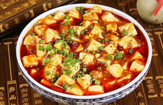 """Đậu hũ Tứ Xuyên làm món ăn đặc sản của vùng Tứ Xuyên - Trung Hoa. Mang hương vị cay đặc trưng , cảm giác bạn sẽ không bao giờ quên nếu bạn đã từng thưởng thức. Sự kết hợp giữa miếng đậu hũ trắng mềm, thịt xay và ớt cay riêng biệt của vùng Tứ Xuyên đã tạo nên một món ăn mang cả hương vị lẫn màu sắc vô cùng bắt mắt Vậy theo bạn, món ăn đậu hũ Tứ Xuyên - Mapo đã được ra đời như thế nào? Món ăn đơn giản từ trong nguyên liệu cho đến cách chế biến này lại trở thành niềm tự hào của người Trung Hoa. Tuy đơn giản nhưng lại chứa đựng hương vị thơm ngon và cả một lịch sử hình thành, phát triển thú vị.Đậu hũ Tứ Xuyênthực chất có tên gốc là Mapo. Trong tiếng Trung Quốc, """"Mapo"""" là từ ghép có ý chỉ một người phụ nữ lớn tuổi và mặt rỗ. Đậu hũ Tứ Xuyên - Món ăn được tạo ra với 7 hương vị hấp dẫn đến vị giác Sở dĩ món ăn có cái tên này là bởi nó gắn liền với truyền thuyết về nhà hàng của bà Chen: Tứ Xuyên xưa kia có một hàng cơm nhỏ do bà Chen Mapo làm chủ. Không ai rõ tên thực của bà là gì, chỉ biết bà từ nhỏ do bị bệnh đã để lại sẹo rỗ trên mặt, nên người ta thường gọi là """"Bà Chen mặt rỗ"""" – tức Chen Mapo. Để xử lý số lượng đậu hũ dư thừa trong kho thực phẩm, Chen Mapo đã nghĩ ra cách kết hợp nó với các nguyên liệu khác nhằm đổi mới món ăn, đưa ra một công thức hoàn toàn mới. Bà đã trộn đậu với thịt heo băm nhỏ cùng rất nhiều gia vị khác nhau, xào chung trên một chiếc chảo lớn. Công thức này mau chóng đem lại tiếng tăm cho nhà hàng của Chen Mapo. Sau này, khi món ăn có mặt tại nhiều nhà hàng lớn, người ta đã đổi tên thành nơi sản sinh ra nó – Tứ Xuyên. Món đậu hũ Tứ Xuyên là sự tổng hòa của nhiều nguyên liệu để cho ra 7 loại hương vị hấp dẫn và kích thích mạnh đến vị giác người dùng đó là: bùi – cay – nóng – tươi – mềm – thơm – giòn. Hãy cùng vào bếp và thực hiện món ăn này với các bước hướng dẫn cùng chúng tôi để cảm nhận những tinh túy trong ẩm thực Trung Hoa nhé! Nguyên Liệu Làm Đậu Hũ Tứ Xuyên 600g đậu hũ non 50g nạc dăm 100g tôm 50g nấm rơm 20g hành tím 20g tỏi 20g ớt sừng khôn"""
