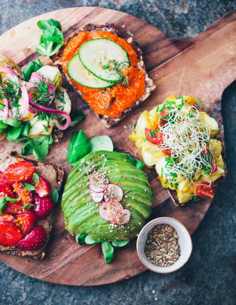 """Smorrebrod với sự kết hợp của lát bánh mì nâu sẫm phủ pate béo ngậy, thịt xông khói đỏ au, cá trích ngọt thơm và lát trứng luộc bùi bùi tạo nên một món bánh truyền thống độc đáo. Người Đan Mạch thường sử dụng món bánh thơm ngon, bổ dưỡng này làm bữa ăn trưa.  """"Smorrebrod"""" trong tiếng Đan Mạch nghĩa là """"bơ và bánh mì"""", nhưng trên thực tế món bánh này ngoài 2 nguyên liệu trên còn sử dụng thêm nhiều nguyên liệu khác nữa tùy theo ý thích của người ăn. Thông thường, trên lát bánh mì sẽ được phủ cá hun khói, thịt nguội, pho mát hoặc patê, hải sản, có thể thêm vài lát trứng luộc… Ngoài ra, họ cũng có thể trang trí món ăn bằng việc những loại đĩa ăn có hình dạng khác nhau và bổ sung thêm những loại rau củ được cắt tỉa kỹ lưỡng.  """"Smorrebrod"""" có nguồn gốc và ra đời như thế nào?  Smørrebrød ra đời từ thế kỷ 19. Lúc này, đối với người nông dân Đan Mạch thì bữa trưa là bữa ăn chính trong ngày. Sau khi ăn bữa trưa xong thì họ thường dùng bánh mì quệt những gì còn sót lại trên đĩa để không lãng phí thức ăn. Lâu dần họ đổi cách ăn, thay vì dùng bánh mì quệt thì người nông dân cho hẳn các nguyên liệu lên bánh và từ đó món Smørrebrød ra đời.  Smorrebrod bao gồm những gì?  Smørrebrød có nghĩa là bơ và bánh mì, nhưng trên thực tế món ăn này không chỉ bao gồm 2 nguyên liệu đơn giản như thế mà còn được đặt thêm rất nhiều các nguyên liệu đa dạng màu sắc khác.  Đầu tiên, người Đan mạch sẽ sử dụng một lát bánh mì. Loại bánh mì này không giống với các loại bánh mì sandwich làm từ bột mì mà lớp bánh mì dùng trong Smørrebrød được làm từ lúa mạch đen nên nó có màu nâu đen chứ không trắng tươi. Đặc biệt, bánh mì Smørrebrød không quá mềm nên rất dễ cắt thành các lát mỏng vừa ăn.  Bánh mì được phết lên một lớp bơ, sau đó cho thêm các nguyên liệu tùy thích như trứng cá muối, phô mai lát, mayonnaise, pa tê gan, thịt jampon mềm, cá trích xông khói, thịt heo quay giòn rụm, hải sản, trứng, cà chua, các loại rau thơm...  Ngoài các nguyên liệu thông thường trên thì món Smørrebrød của Đan Mạch còn được c"""