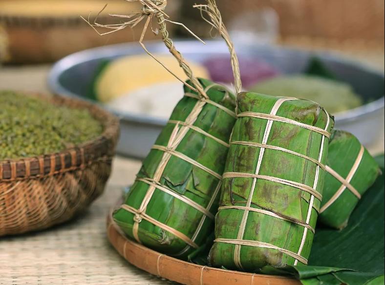 Bánh tét, có nơi gọikhác còn gọi là bánh đòn (tùy theo vùng miền khác nhau tên gọi cũng bị ảnh hưởng). Là một loại bánh trong ẩm thực của cả người Việt và một số dân tộc ít người ở miền Nam và miền Trung Việt Nam. Chúng có nét tương đồng của bánh chưng ở Miền Bắc về nguyên liệu, cách nấu, chỉ khác về hình dáng và sử dụng lá chuối để gói thay vì lá dong. Vì vậy nó cũng được sử dụng nhiều nhất trong dịp Tết Nguyên đán cổ truyền của dân tộc Việt Nam với vị trí không khác bánh chưng. Nhưng cũng có nhiều bánh tét nhân chuối hay đậu đen được làm hay là bán quanh năm. Bánh tét ngày Tết thường để lâu được vài ngày, được nấu vào đêm giao thừa hoặc xa hơn để những ngày Tết có thể dùng để ăn với dưa món và thịt kho . Đây thường là bánh tét nhân mặn với thịt, mỡ và đậu xanh, và dùng cho nhiều người ăn Ngoài ra, còn có bánh tét nhân ngọt với nhân chuối hoặc đậu xanh, loại to dùng cho nhiều người ăn hoặc loại nhỏ dùng cho một người ăn. Nếu bạn chưa được trải nghiệm những công đoạn này diễn ra như thế nào thì hãy cùng An Thành tìm hiểu về cách làm bánh tét ngày Tết bằng lá chuối hoặc lá dong cực ngon, xanh, đẹp mắt, ăn là nghiền ngay sau đây nhé. Nguyên liệu làm bánh tét: 800 g nếp 400 g đậu xanh nguyên vỏ 400 g thịt ba rọi (ba chỉ) ¼ thìa cà phê muối 1 thìa cà phê nước mắm 1 thìa cà phê đường ¼ thìa cà phê bột nêm/ vị tinh 1 thìa cà phê tiêu (xay/ nguyên hạt) 2 củ hành tím đập dập Dụng cụ thực hành: Lá chuối / lá dong Lạt tre Nồi cỡ lớn / nồi áp suất Khay/ mâm rộng Hướng dẫn sơ lược quá trình hình thành bánh tét: Bước 1: Chuẩn bị Đậu và nếp ngâm từ 4-8 tiếng, vớt ra để ráo rồi xóc với chút muối. Lạt tre ngâm 8-10 tiếng cho mềm. Lá chuối rửa sạch, chần qua nước sôi để ráo, lau khô. Thịt rửa sạch, để nguyên tợ và cắt dải dài, ướp gia vị 15-20 phút. Bước 2: Gói bánh tét Trải lá chuối lên khay/mâm rộng. Đổ gạo nếp lên lá, dàn mỏng thành lớp theo chiều ngang. Làm tương tự với đậu. Trải thịt vào giữa. Phủ một lớp đậu và gạo nếp phủ cuối cùng. Lưu ý dàn nếp phủ đều đậu và thịt. Cuốn sấp